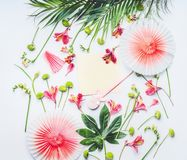 Tomt hälsa kort som är falskt upp med papperspartifans, tropiska sidor och exotiska blommor på vit bakgrund, bästa sikt Lekmanna- royaltyfri bild