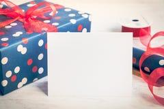 Tomt hälsningvitkort Slågna in gåva och inpackningsmaterial över en vit wood bakgrund tappning för stil för illustrationlilja röd Arkivfoto