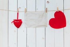 Tomt hänga för röd hjärta och för gammalt papper på klädstrecket på den wood whien Fotografering för Bildbyråer