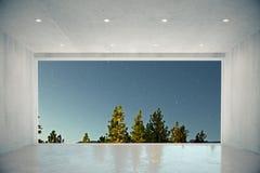 Tomt konkret rum med det stora fönstret med blå himmel och skogen tävlar Arkivfoto