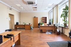 Tomt kontorsutrymme med skrivbord, kabinetter och blommor, når att ha flyttat sig, inget fotografering för bildbyråer