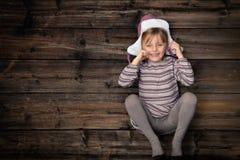 Tomt kopieringsutrymme för text eller för logo i vertikalt mörkt tappningträ för bästa sikt Härlig lycklig barnflicka i homewear  arkivbilder