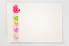 Tomt kort med färgrika hjärtor över rosa band Arkivfoto