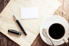 Tomt kort med pennan och koppen kaffe royaltyfri foto