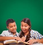 Tomt kritabräde bak latinamerikansk pojke och flickan som har roligt studera royaltyfria foton