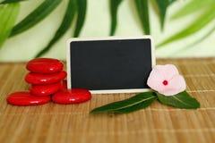 Tomt kritisera för att skriva ett meddelande bredvid ordnade röda kiselstenar i zenlivsstil på det wood golvet för bambu med en p Royaltyfri Fotografi