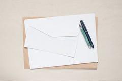Tomt kuvert och ark av papper på tabellen Royaltyfria Foton