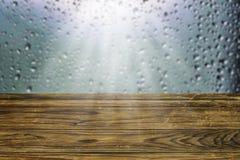 Tomt lantligt träbräde eller gammalt ridit ut trädgårds- bästa suddigt fönster för tabell med regndroppar Royaltyfri Bild