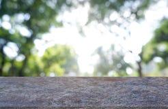 Tomt marmorera stenen tabell som är främst av abstrakt suddig gräsplan av trädgården och träd Bakgrund För montageproduktskärm el royaltyfri foto