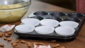 Tomt papper bildar för muffin och muffin i ett metallmagasin lager videofilmer