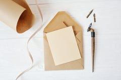 Tomt papper för modellferiebokstav och ett kuvert med pennan på den wood tabellen, med utrymme för din text, bästa sikt royaltyfria foton