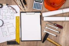 Tomt papper, husplan, hjälm och arbetsavgifter royaltyfri foto
