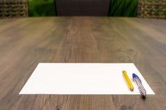 Tomt papper med pennan och blyertspennan på trätabellen, raka linjer Arkivfoto
