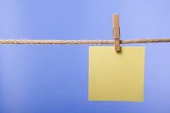 Tomt papper noterar att hänga på repet med kläderben, kopieringsutrymme arkivbild