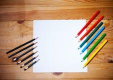 Tomt papper och grafit och färgrika blyertspennor Arkivfoto