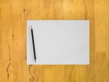 Tomt papper och svart blyertspenna på trätabellen Royaltyfria Foton