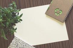Tomt papper på en wood tabell med anteckningsboken, växten och en bok Royaltyfria Bilder