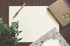 Tomt papper på en wood tabell med pennan, anteckningsboken, växten och en bok Royaltyfria Foton