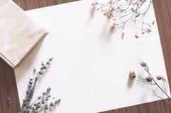 Tomt papper på tabellen med boken och torkade blommor Royaltyfri Bild
