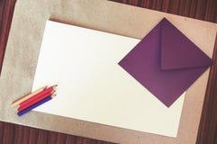Tomt papper på tabellen med kuvertet och färgpennor Arkivbild