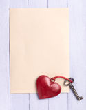 Tomt pappers- ark med en tappninghjärta och en gammal tangent Royaltyfri Foto