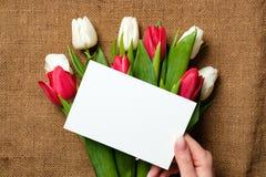 Tomt pappers- kort i kvinnas händer på lantlig säckvävkanfas med tulpanblommor Hälsningkort för internationell kvinnas dag, mödra arkivfoton