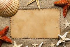 Tomt pappers- kort och olik skal och sjöstjärna på strandsand royaltyfri fotografi