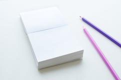 Tomt pappers- kvarter och två blyertspennor på ljus bakgrund Royaltyfri Fotografi
