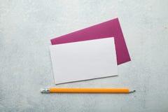 Tomt pappkort med ett rosa kuvert på en vit bakgrund för tappning arkivfoto