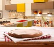 Tomt pizzabräde med bordduken på den inre suddiga bakgrunden för tabell och för kök royaltyfri bild
