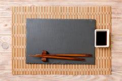 Tomt rektangulärt svart kritiserar plattan med pinnar för sushi och soya på träbakgrund B?sta sikt med kopieringsutrymme royaltyfria bilder