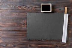 Tomt rektangulärt svart kritiserar plattan med pinnar för sushi och soya på träbakgrund B?sta sikt med kopieringsutrymme arkivfoto