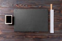Tomt rektangulärt svart kritiserar plattan med pinnar för sushi och soya på träbakgrund B?sta sikt med kopieringsutrymme arkivfoton