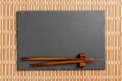 Tomt rektangulärt svart kritiserar plattan med pinnar för sushi på träbakgrund B?sta sikt med kopieringsutrymme arkivfoto