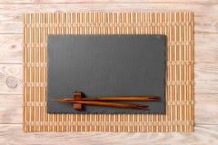 Tomt rektangulärt svart kritiserar plattan med pinnar för sushi på träbakgrund B?sta sikt med kopieringsutrymme royaltyfria foton