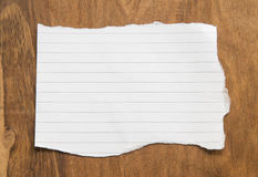Tomt sönderrivet papper på träbakgrund Arkivfoton
