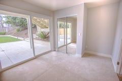 Tomt sovrum med den glass dörren för stor slidimg till trädgården i ett sydliga Kalifornien hem royaltyfria bilder