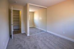 Tomt sovrum med spegelförsedda hemliga dörrar och matta arkivbild