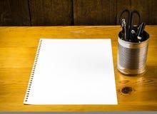 Tomt stycke av papper på den wood tabellen med pennor i metallcan royaltyfri fotografi