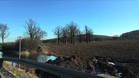 Tomt svart fält, grönt fält, snö och att smälta vatten i tidig vår Sikt från rörande bilfönster stock video