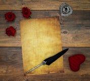 Tomt tappningkort med den röda omfamninghjorten, röda rosor, färgpulver och vingpennan på tappningeken, förälskelsebokstav på ant fotografering för bildbyråer