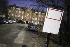 Tomt tecken med gammal byggnad i bakgrunden Arkivfoto