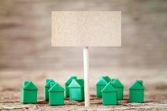 Tomt tecken med mini- gröna hus Arkivfoto