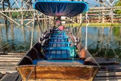 Tomt träfartyg på en bambuflotte n sjön med att reflektera av bron på vattenbakgrunden royaltyfria foton