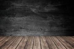 Tomt trägolv med mörk betongväggbakgrund, för produ royaltyfri fotografi