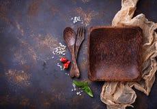 Tomt träplatta, bestick, salt, peppar och basilika Arkivbilder