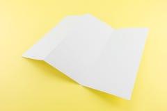Tomt Trifold vitt mallpapper på gul bakgrund med sof Royaltyfri Foto