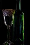 Tomt vinflaska och rött vinexponeringsglas på svart bakgrund Royaltyfri Bild