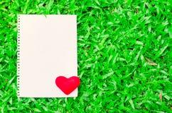 Tomt vitt anmärkningspapper med röd hjärta på glass bakgrund Arkivfoton
