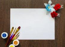 Tomt vitt ark av papper för din text på en mörk wood tabellbakgrund Det finns färgade målarfärger, borstar och blommar runt om de arkivfoton